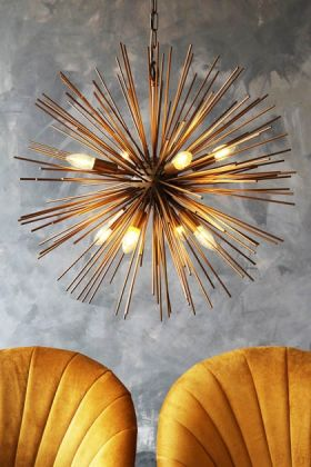 lifestyle image of starburst brass beam pendant lamp with gold velvet chairs underneath and grey wall background