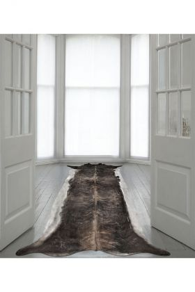 lifestyle image of super long stretched cowhide rug in white room with white doors and bay windows