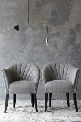 lifestyle image of the lovers herringbone tweed chair - garson grey with gold and black industrial ceiling light and grey wall background