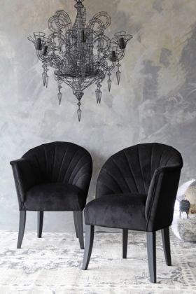 lifestyle image of the lovers velvet chair -back to black with black wire chandelier above and grey wall background