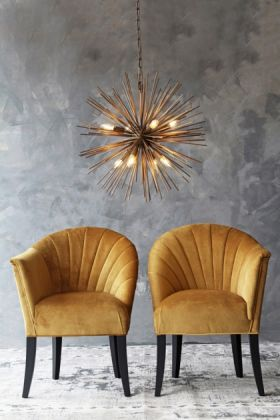 lifestyle image of the lovers velvet chair -golden glow with gold star ceiling light above and grey wall background