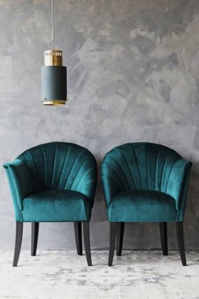 lifestyle image of the lovers velvet chair -ocean deep green with gold and green pendant ceiling light and grey wall background
