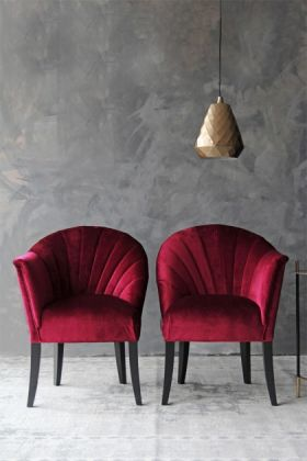 lifestyle image of the lovers velvet chair -pinot noir red with gold pendant light above with grey wall background