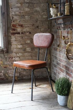 lifestyle image of The Stockard Leather Dining Chair under shelf and with plant in pot on wooden flooring and distressed brick wall background