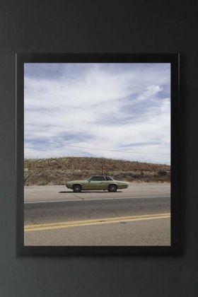 lifestyle image of Unframed Bisbee Roadside Art Print in black frame on dark grey wall background