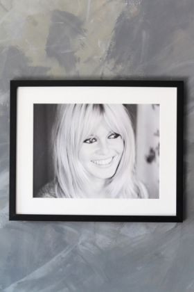 lifestyle image of Unframed Paea Art Print - Brigitte Bardot black and white photograph in black frame on distressed grey wall background