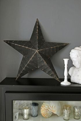 lifestyle image of vintage metal star - black on black cabinet with white candlestick and white bust ornament