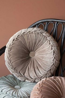 Lifestyle image of the Vintage Style Velvet Rouched Round Cushion in Taupe on black rattan chair with emanuella painted wall background