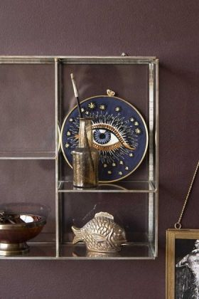 Close-up lifestyle image of the Wall Mounted Glass Shelf Unit filled with ornaments on purple painted wall background