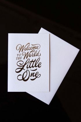 lifestyle image of Welcome to the World Little One Greeting Card - Pink with envelope on black table