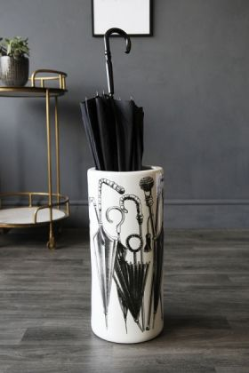 lifestyle image of white ceramic umbrella stand with umbrella inside and drinks trolley in background on wooden flooring