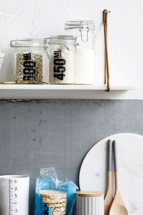 lifestyle image of White Marble Shelf with jars on top and crowded kitchen counter below on grey wall