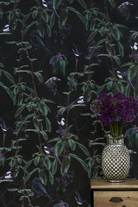 lifestyle image of witch & watchman folia wallpaper - dark with wooden table and grey vase with purple flowers in