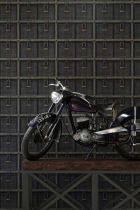 lifestyle image of andrew martin attic collection basket wallpaper - 2 colours available with large motorbike on wooden table