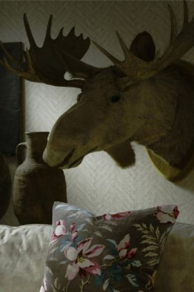 lifestyle image of andrew martin attic collection parquet wallpaper - 4 colours available with moose head ornament on wall, patterned cushion and bottle neck vase
