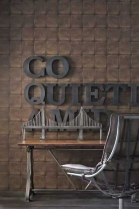 lifestyle image of andrew martin engineer collection - colonial 'quilted leather' wallpaper - 2 colours available with 'go quiet' sign on wall and wooden table with leather and metal desk chair