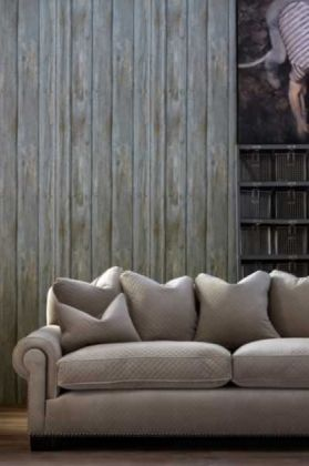 lifestyle image of andrew martin engineer collection - timber wallpaper - 2 colours available  behind grey sofa and next to black stair case