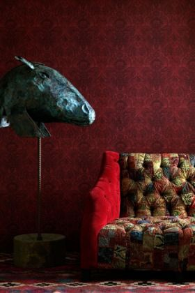 lifestyle image of andrew martin kew wallpaper -  sand, stone or red with patterned sofa and blue animal head on stand