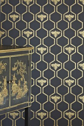 detail image of barneby gates honey bees wallpaper - gold on charcoal with black and gold cabinet