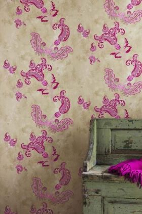 lifestyle image of barneby gates paisley wallpaper - hot pink on tea stain with distressed green bench with pink cushion in front