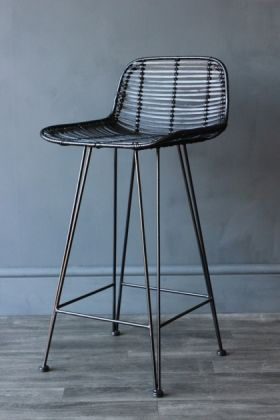 lifestyle image of black rattan bar stool on dark wooden floor and dark wall background