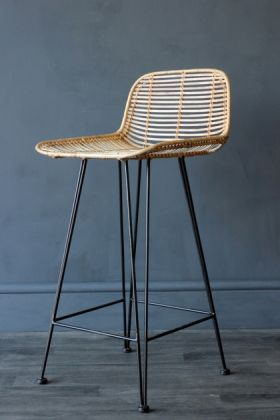 lifestyle image of blonde rattan bar stool on grey flooring and dark wall background