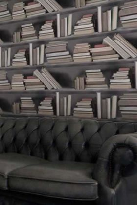 lifestyle image of young & battaglia bookshelf wallpaper - vintage and dark grey sofa in front