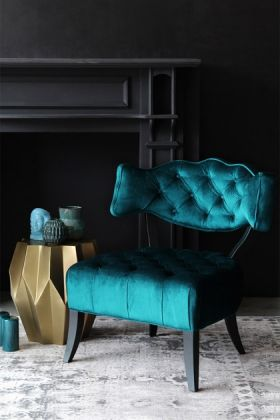 lifestyle image of cloud velvet chair - ocean deep green with gold side table and blue ornaments with black fireplace in background