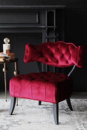 lifestyle image of cloud velvet chair - pinot noir red with side table and table lamp on grey patterned rug and black wall background