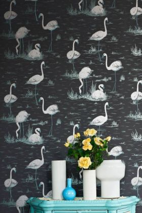 lifestyle image of cole & son contemporary restyled - flamingos wallpaper - 5 colours available behind blue side table with white vases and yellow flowers