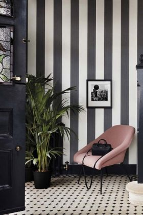 lifestyle image of Cole & Son Marquee Stripes Collection - Jaspe Stripe Wallpaper - Charcoal with black door and pink armchair and plant