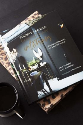 lifestyle image of Extraordinary Interiors by Jane Rockett & Lucy St George with leopard print book and black mug on black table