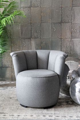 lifestyle image of gallery herringbone tweed cocktail chair - garson grey with disco balls and plant on patterned grey rug and grey tile wallpaper background