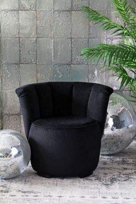 lifestyle image of gallery velvet cocktail chair - back to black with disco balls and plant on grey patterned rug and grey tiled wallpaper background