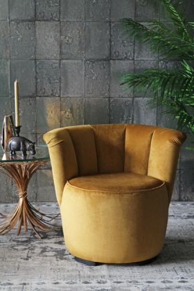 lifestyle image of gallery velvet cocktail chair - golden glow with gold side table and hippo candle holder and plant on grey patterned rug on grey tiled wallpaper background