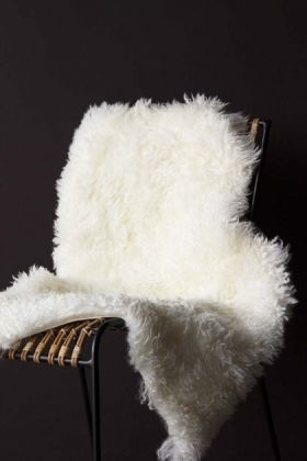 lifestyle image of genuine sheepskin rug - curly bone white on natural rattan chair and dark wall background
