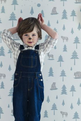 lifestyle image of hibou home into the wild children's wallpaper with little boy with panted nose