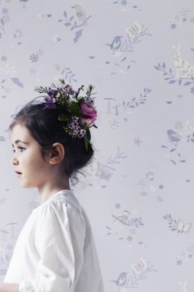 lifestyle image of hibou home secret garden children's wallpaper with little girl with flowers in her hair
