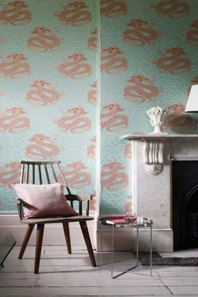 lifestyle image of matthew williamson celestial dragon wallpaper with marble effect fireplace and wooden chair with pink velvet cushion