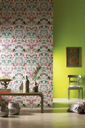 lifestyle image of Matthew Williamson Menagerie Wallpaper - 5 Colours Available with green wall and wooden table with ornaments on and chair in corner