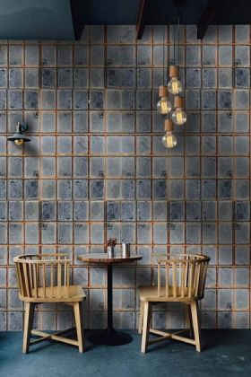 lifestyle image of Mind The Gap The Factory Collection - Foundry Wall Wallpaper with two wooden chairs with side table and gold ceiling light