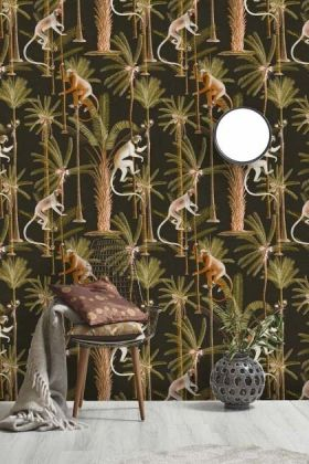 lifestyle image of Mind The Gap The Rediscovered Paradise - Barbados Wallpaper - Anthracite with chair covered with blanket and cushions with white globe ceiling light above grey vase on floor