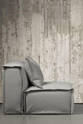 lifestyle image of nlxl con-06 concrete wallpaper by piet boon with large grey sofa on grey flooring