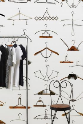 lifestyle image of nlxl dro-02 obsession hangers wallpaper by daniel rozensztroch with black metal chair and clothing rack with t shirts on