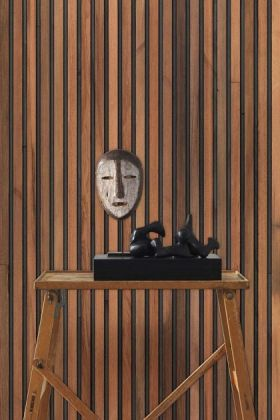 lifestyle image of NLXL TIM-01 Timber Strips Wallpaper by Piet Hein Eek with wooden table with black box ornament and brown and white face ornament on top