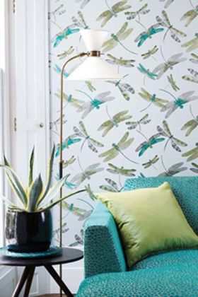 lifestyle image of matthew williamson dragonfly dance wallpaper - 4 colours available behind blue sofa with green cushion and black side table with plant