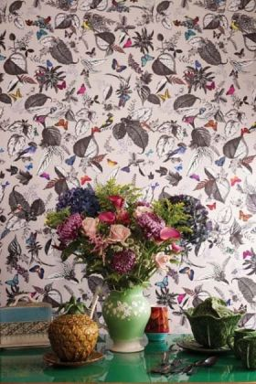 lifestyle image of osborne & little bird song wallpaper with green vase and flowers on green table