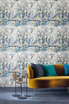 lifestyle image of Osborne & Little Japanese Garden Wallpaper - 3 Colours Available with yellow sofa with blue cushions and black side tables with wooden ornaments on