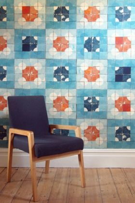 lifestyle image of smink things quarter circle blue tile wallpaper with blue and wood chair