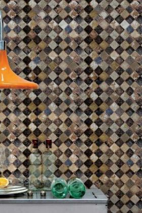 lifestyle image of solera chess wallpaper with orange ceiling light over grey table with green glasses on